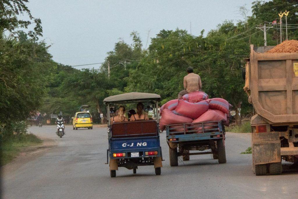 Cambodia travel tips and advice -tuk tuk, man riding on the back of potato sacks on truck
