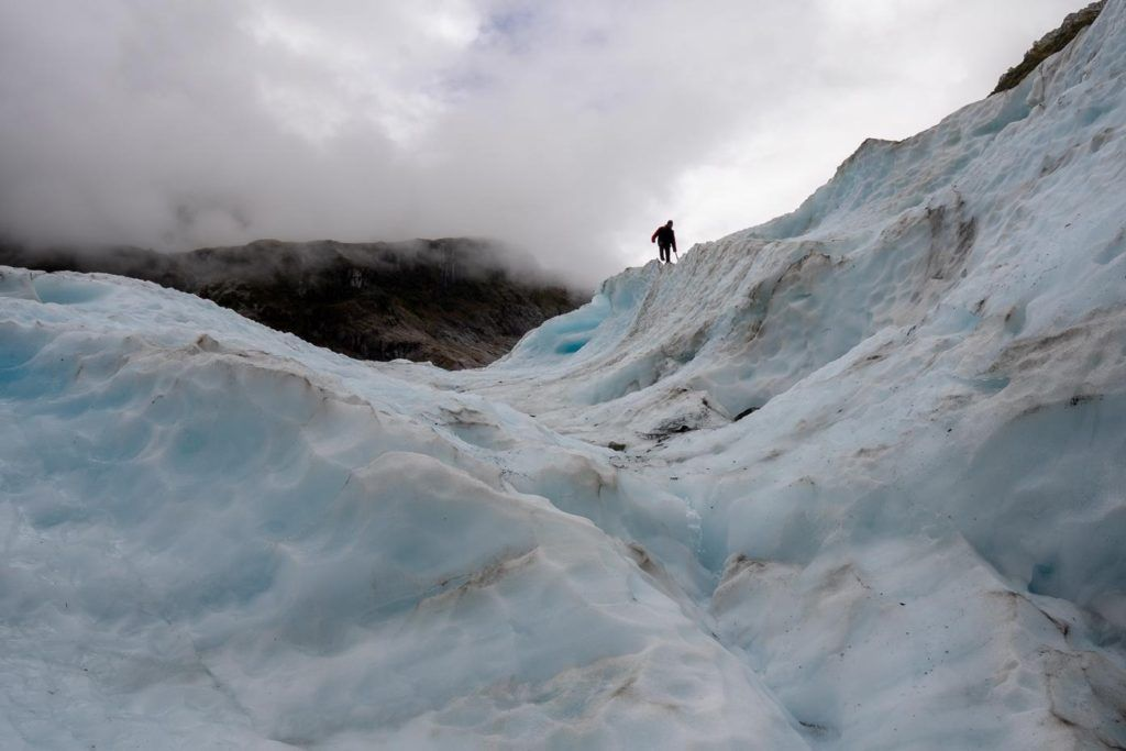 Man watching the weather on Fox Glacier