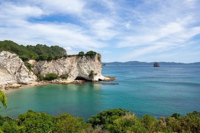 Cliff face and crystal clear water in the Coromandel, a spectacular area for New Zealand Road trips